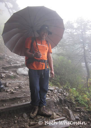 Tobgay with umbrella along trek