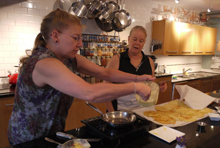 Kim making crepes with Diane looking on at Diane's Market Kitchen