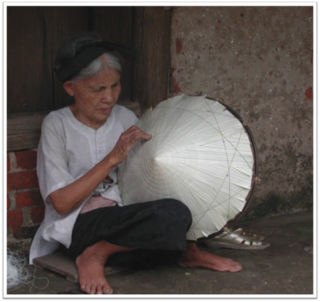 Woman making conical hat near Hanoi