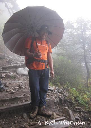Tobgay with umbrella along trek